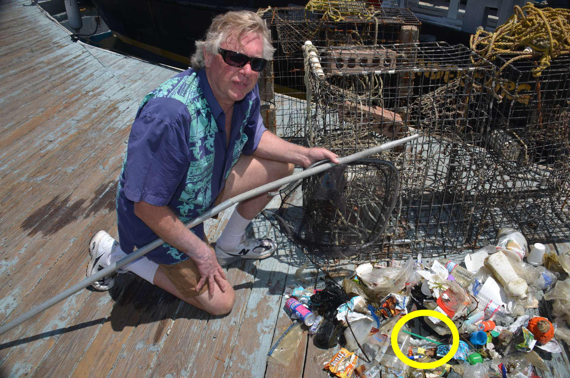 Ocean Defender Kurt Lieber on dock with debris hauled in, including plastic straw (see circle)