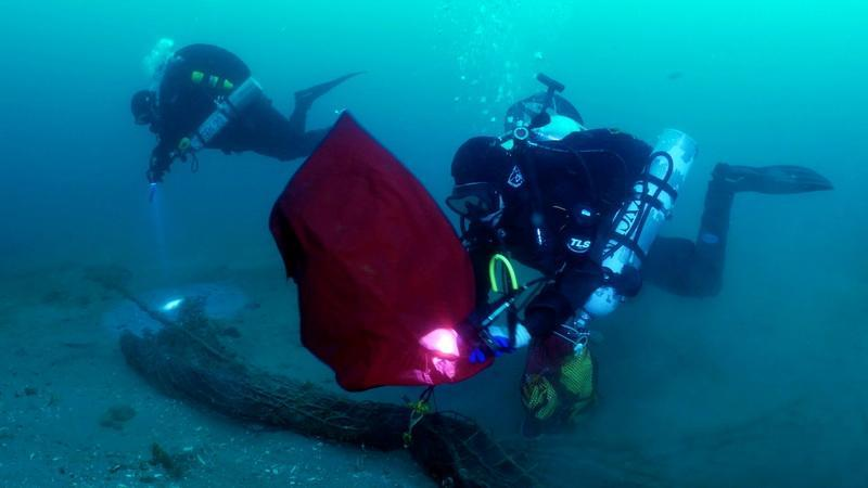 ODA technial divers Jeff Larsen and Kim Cardenas work to remove ghost net