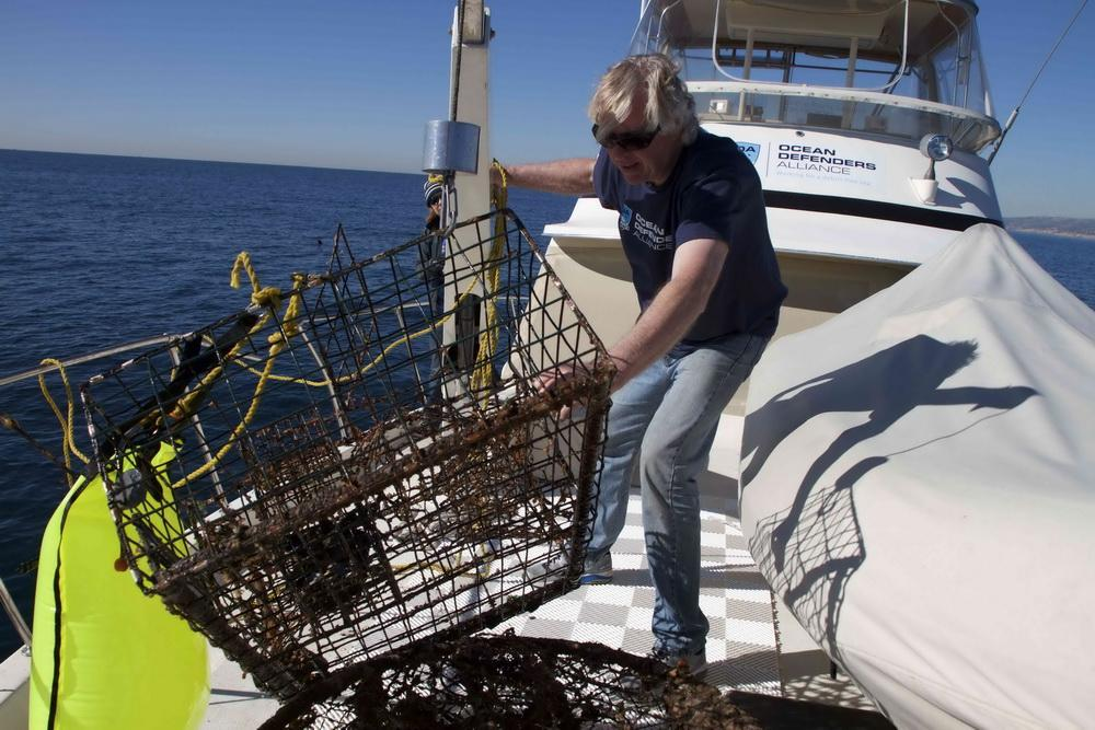 ODA Captin Kurt Lieber pulls an abandoned lobster trap onto boat deck.