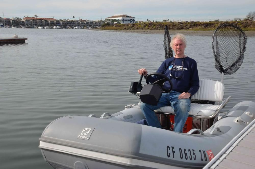 ODA Volunteer on small boat outfitted for surface cleanup